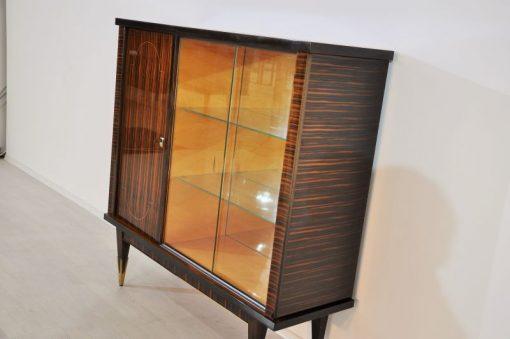 einzigartiges Makassar-Furnier mit tollen Details Originalfüße mit Messingapplikationen Glas-Schiebetür und Glasböden Verspiegelte Rückwand